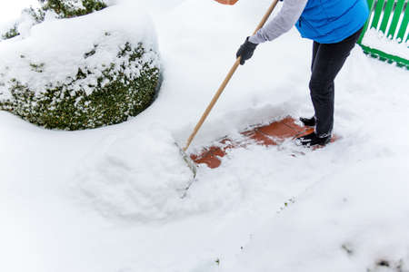 shoveling: a woman shoveling the new snow from a path. onset of winter Stock Photo