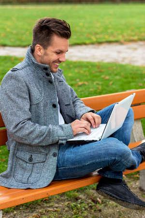 edv: un uomo con un computer portatile seduti su una panchina