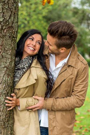 joie: ein junges, lachte liebtes Frau auf der Suche hinter einem Baum Lizenzfreie Bilder