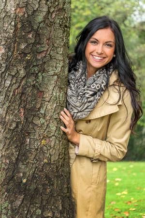 joie: Eine junge Frau schaut heraus von hinten einen Baum Lizenzfreie Bilder