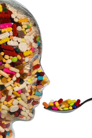 investigated: a head made of glass filled with many tablets. photo icon for drugs, abuse and addiction tablets. Stock Photo