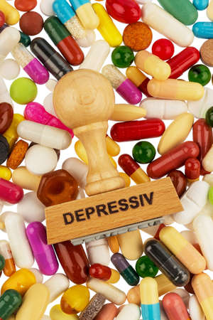 therapie: stamp on colorful tablets, symbolic photo for depression, therapy and psychotropic drugs
