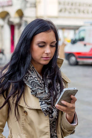 foreign: a young woman writing a text message on his cell phone. communication with a smart phone