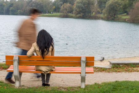 a young woman sitting on a park bench photo