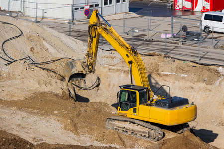 contruction: excavator on a construction site. excavator bucket with soil, earthworks. Stock Photo