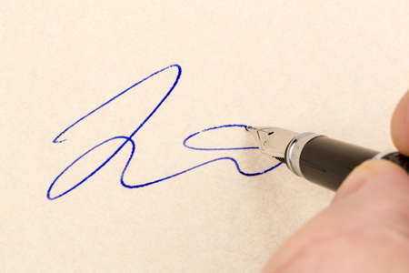notieren: a contract or document shall be signed by hand with a fountain pen. Stock Photo