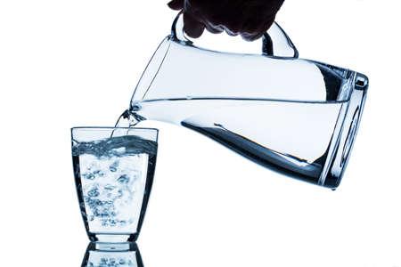 vasos de agua: agua pura se vacía en un vaso de agua de una jarra. agua potable