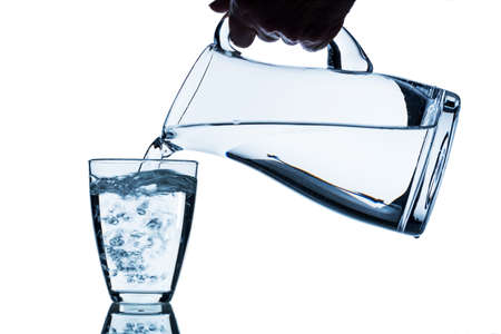 purely: pure water is emptied into a glass of water from a jug. fresh drinking water