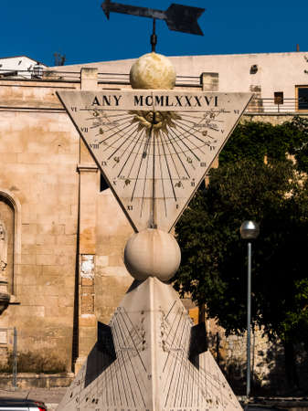 changing seasons: a sundial in the city of palma mallora, spain.