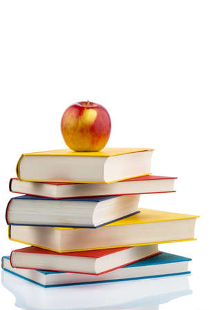 an apple lying on a pile of books. symbolic photo for healthy, vitamin-rich food in the school break. Stock Photo