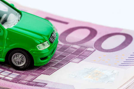 green model car on banknotes, symbolic photograph for car purchase, financing and costs