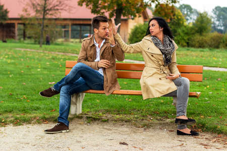 voltages: a young couple sitting on a park bench and fight Stock Photo
