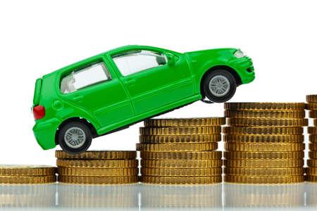 een model auto staande op munten. stijgende kosten voor auto benzine prijs, verzekeringen en belastingen. Stockfoto