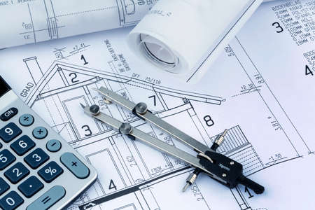 an architects blueprint with a calculator. symbolic photo for funding and planning of a new home.