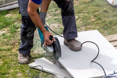 a tiler at work. cuts plates with a cut-off wheel photo