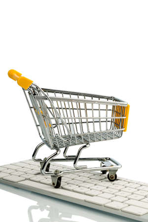 consumerist: shopping cart is on the keyboard of a pc, symbolic photo for online shopping and consumer behavior