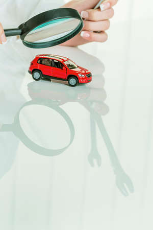 workshop service: a model of a car is examined by a doctor. photo icon for workshop, service and car purchase.