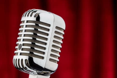 micro recording: an old retro microphone in front of red velvet background. Stock Photo