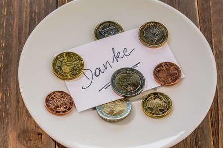recoger: un plato de monedas por consejo o cuota para inodoros. en idioma alemán Foto de archivo