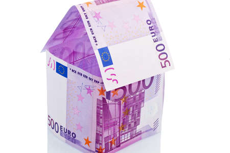 a house built with money seem on a white background. building savings, house building and home buying. Stock Photo