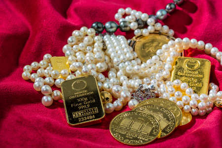 gold bars: gold coins and bars with decorations on red velvet. photo icon for wealth, luxury, wealth tax.