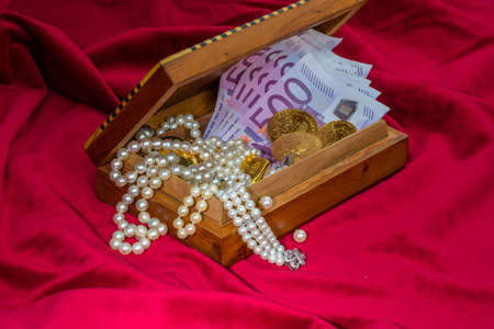 inheritance: gold coins and bars with decorations on red velvet. photo icon for wealth, luxury, wealth tax.