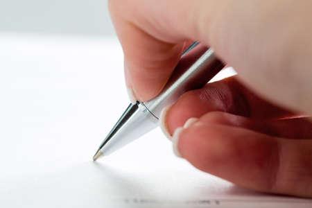 testament schreiben: eine Hand mit einem Füllfederhalter in untrerschrift im Rahmen eines Vertrags oder Testament.