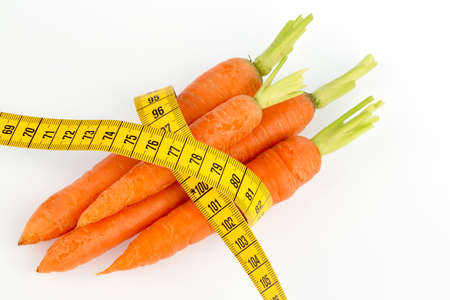 organically grown carrots with tape measure. fresh fruit and vegetables is always healthy. symbolic photo for healthy diet. Stock Photo