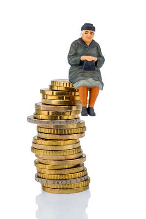 pensions: pensioner sitting on a pile of money, symbolic photo for pensions, retirement, old age