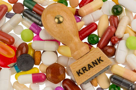 suspected: stamp on colorful tablets, symbolic photo for illness, sick leave and drugs Stock Photo