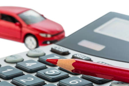 motor cars: a car and a red pen lying on a calculator. cost of gasoline, wear and insurance. car costs are not paid by commuter tax. Stock Photo