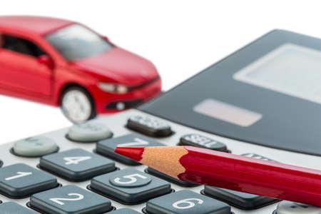 een auto en een rode pen liggend op een rekenmachine. kosten van benzine, slijtage en verzekeringen. autokosten worden niet betaald door forensen belasting. Stockfoto