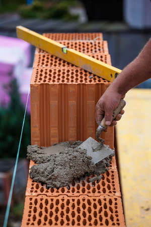 botch: anonymous construction worker on a construction site in home building erected a wall of bricks. solid brick wall of a house. icon image for undeclared work and botch