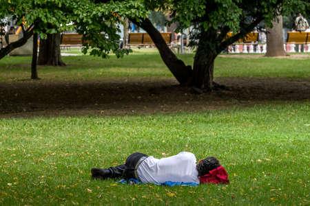 overtired: man sleeping in a park  in linz, austria.