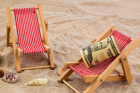 last minute: beach chair with dollars on the sandy beach. symbolic photo for cost of travel, vacation, holidays. save on vacation Stock Photo