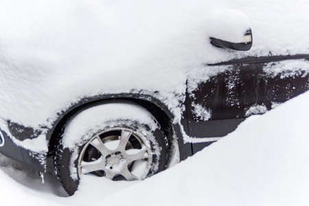 car lots: lots of snow on a parked car in the winter. Stock Photo