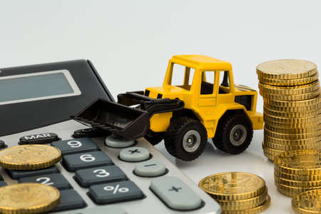 doldrums: cost accounting in the construction industry and the construction industry. higher higher prices for road and residential construction. excavator with coins and calculator Stock Photo