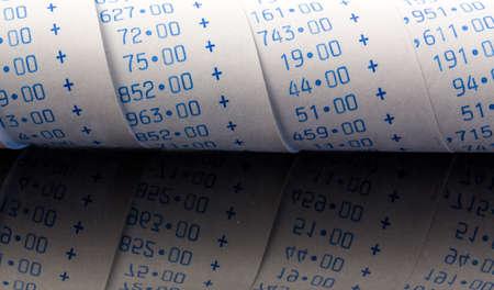 le strisce di calcolo di una calcolatrice su uno sfondo bianco. Foto simbolica per il controllo, la contabilità, fiscalità e finanza