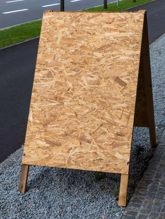 advertising signs: an empty poster stands made of pressed wood shavings. copy space and background