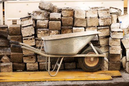 carretilla: carretilla y grandes piedras, símbolo de la construcción, la obra de construcción, los nuevos edificios