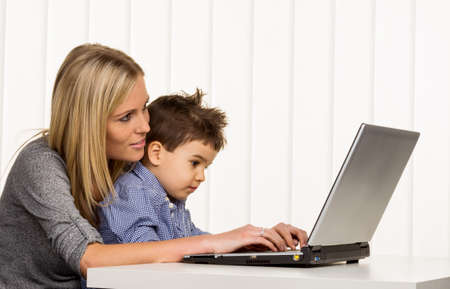 mother and son on the computer, symbol of home, family and career, double burden Stock Photo