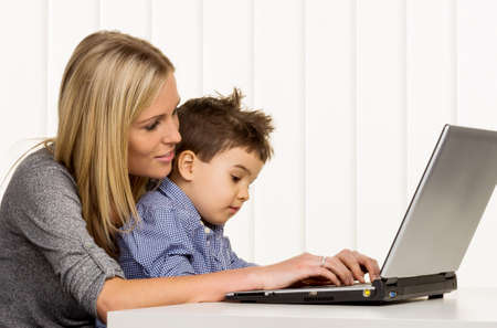 burden: mother and son on the computer, symbol of home, family and career, double burden Stock Photo