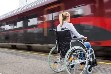 Een jonge vrouw zit in een rolstoel op een treinstation