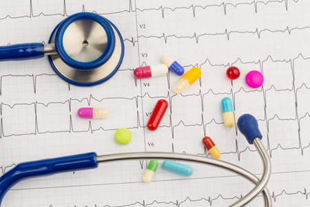 blood circulation: several tablets lie on an ekg.