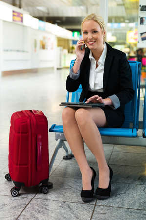 foreign country: a businesswoman using her phone and a tablet computer at an airport.
