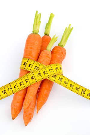 thinness: organically grown carrots with tape measure. fresh fruit and vegetables is always healthy. symbolic photo for healthy diet. Stock Photo