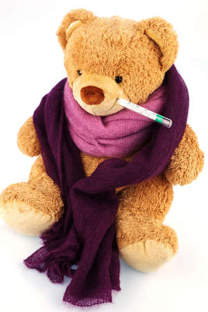 bedridden: a bear plush with a thermometer in his mouth. symbolic photo for chill, flu and fever