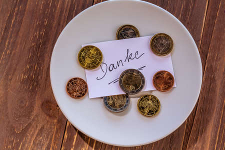 contributions: a plate of coins for tips or fee for toilets. in german language