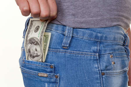 pulling money: the hand of a young woman pulling a dollar money bill out of pocket of her jeans Stock Photo