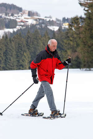 snowshoeing: elderly man in winter snowshoeing Stock Photo